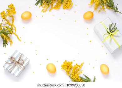 Easter concept frame with eggs, mimosa flowers and gifts. Top view composition. Copy space