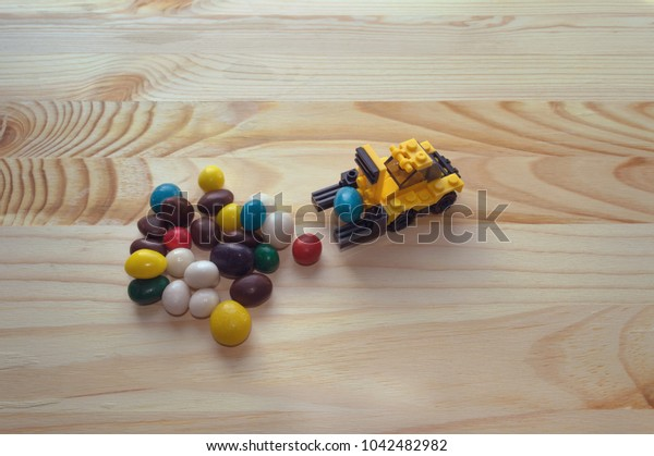 Easter concept of gathering candies with toy loader on wooden background