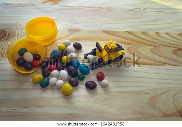 easter concept with toy loader and scatterred candies on wooden background
