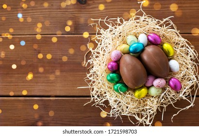 easter, confectionery and holidays concept - chocolate eggs and candies in straw nest on wooden background
