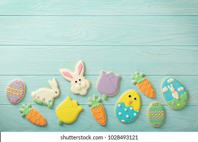 Easter cookies, bunnies and eggs on blue table top view on light blue background