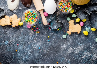 Easter cooking background, dough and indredients, cuts for cookies and colored sugar décor for baking on dark background, The process of making  cookies, series photo, top view, flat lay, copy space