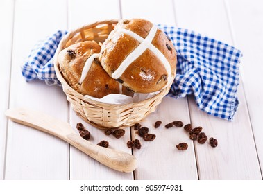 Easter cross-buns in a rustic woven basket on white wooden background