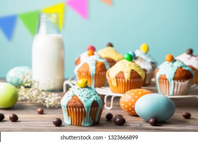 Easter cupcakes glazed with colorful sugar, sprinkles and chocolate with a bottle of milk and painted easter eggs  on a rustic wooden table against a turquoise background with pennants