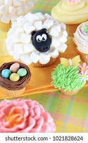 Easter cupcakes. A marshmellow sheep, a bird's nest with Easter eggs, and floral cupcakes decorated with marzipan butterflies.