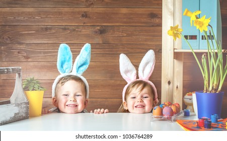 Easter day. Modern Family preparing for Easter. Kids painting eggs on wooden background. Having fun on Easter egg hunt. Child boy and girl wearing bunny ears and painting eggs. colorful eggs.