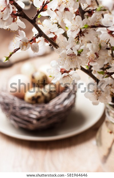 Easter decoration. blossoming branch, nest with eggs on a wooden background