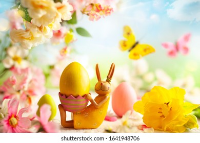 Easter decoration with bunny, Easter eggs and beautiful spring flowers on a blurred light background. Easter concept with copy space.