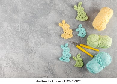 Easter decoration, bunny rabbits made of crochet colorful yarn ongrey texture background. Homemade decor. Top view. Spring Easter holydays concept.