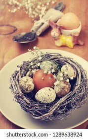 Easter decoration. Chicken and quail eggs in a nest, tulips on a wooden background
