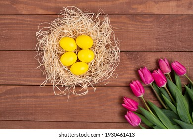 Easter decoration, colored yellow eggs in a nest on wooden background with pink tulips near. Happy Easter. Trendy colour 2021.