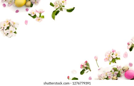Easter decoration. Frame of pink flowers apple tree, colored easter eggs and quail eggs on white background with space for text. Top view, flat lay