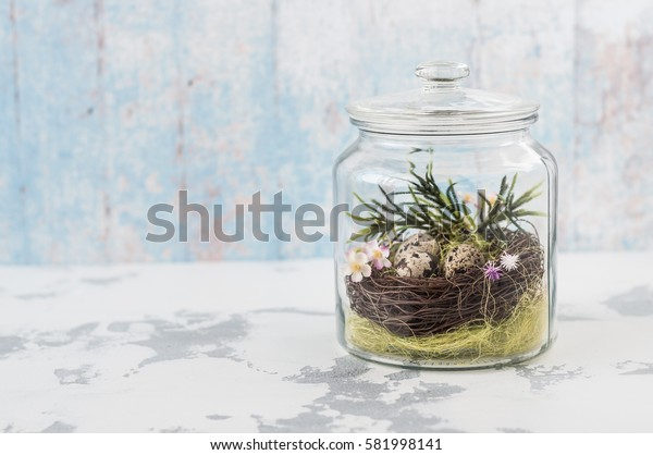 Easter Decoration: a Glass Jar with a Nest, Hay, Flowers, Quail Eggs, copy space for your text