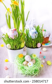 Easter decoration with green grass,flowers,eggs,cake and birds