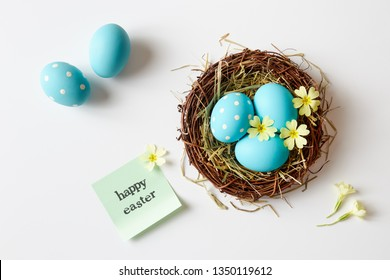 Easter decoration with nest, eggs and spring flowers. Blue Easter eggs in nest with 'Happy Easter' message.