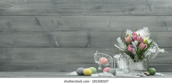 easter decoration with pink tulip flowers, vintage birdcage, pastel colored eggs.retro style toned picture