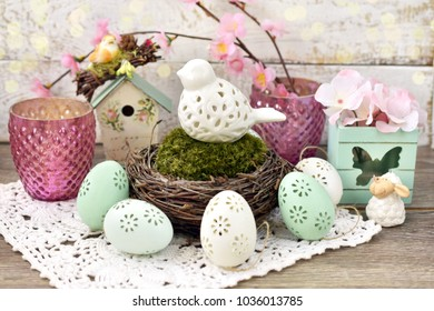 easter decoration with porcelain bird in nest with moss and eggs