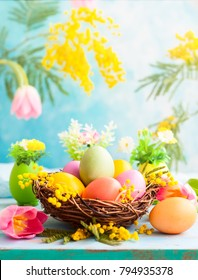 Easter decoration with  spring flowers and colorful dyed eggs in nest