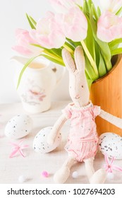 Easter decoration with vintage rabbit toy and eggs on a white wooden background