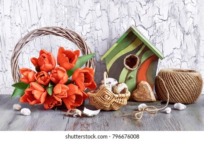 Easter decorations on gray rustic background. Arrangement with wooden wreath, red tulips, birdhouse, quail eggs and brown cord.
