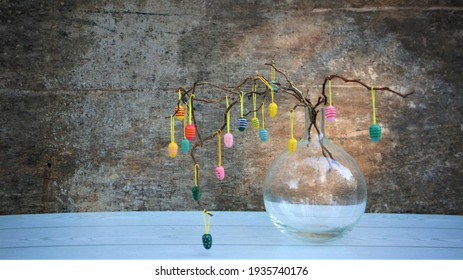 Easter dekorative eggs on tree branches.  Easter tree in vase with colorful eggs on a grey rustic background