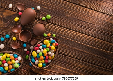 easter dessert tasty chocolate egg with color candy dragee on wooden table. top view