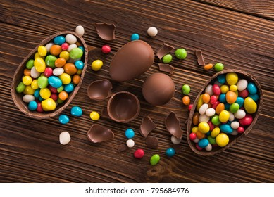 easter dessert tasty chocolate egg with color candy dragee on wooden table