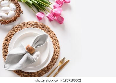 Easter dinner with eggs, bunny, festive tableware and pink tulips on white table. Top view. Copy space.