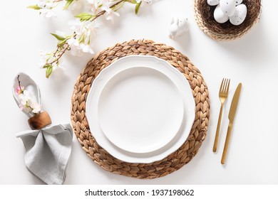 Easter dinner with eggs, bunny, festive tableware and blooming spring flowers on white table. Top view.