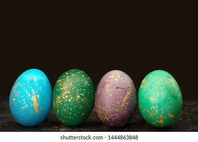 Easter dyed eggs on black background. Luster shiny golden colors. Modern and contemporary style. Copy space concept.