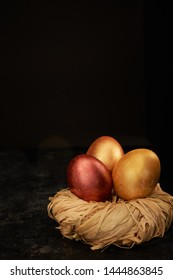 Easter dyed eggs on dark background. Luster shiny golden colors.