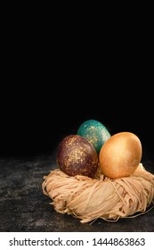 Easter dyed eggs on dark background. Luster shiny golden color eggs in a nest