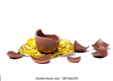 Easter egg broken into small pieces, half the egg is on its gold foil wrapping.