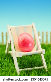 Easter egg in deckchair as Easter holidays. Concept on a green meadow