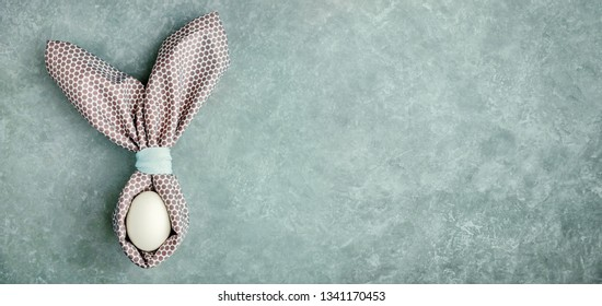 Easter egg decorated with napkin in shape of rabbit ears. Festive easter background