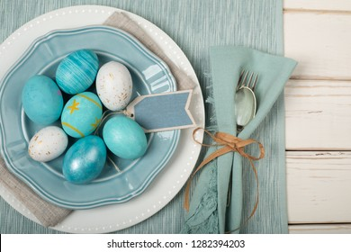 Easter Egg Dinner Place Setting in Nautical Colors of Teal Blue and Off Whites with Plates, Silverware, cloth Napkins and a Name Tag on Rustic White Board Table.  Horizontal flatlay taken from above