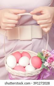Easter Egg. Girl holding a basket with Easter eggs. Easter eggs lying in a basket. Easter ideas. Happy easter.Toned image.