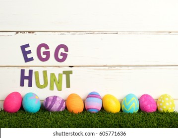 Easter Egg Hunt Invitation with Colorful Dyed Eggs in a line on grass and against White Shiplap Board Background with room or space for your words, copy, text or letters.  It's a horizontal side view