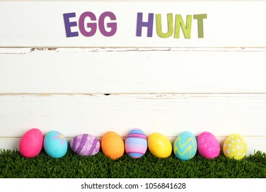 Easter Egg Hunt Invite with Colorful Dyed Eggs in a line on grass and against White Shiplap Board Background with room or space for your words, copy, text or letters.  A horizontal crop from side view