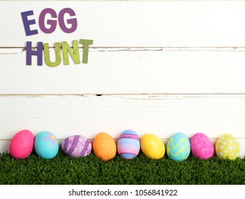 Easter Egg Hunt Invite with Colorful Dyed Eggs in a line on grass and against White Shiplap Board Background with room or space for your words, copy, text or letters. A horizontal crop from side