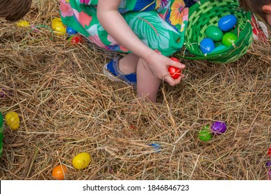 The Easter Egg Hunt is on the way, with kids filling their baskets with plastic candy-filled eggs. The little girl tries to put as many eggs as possible in her basket while searching for a golden egg.