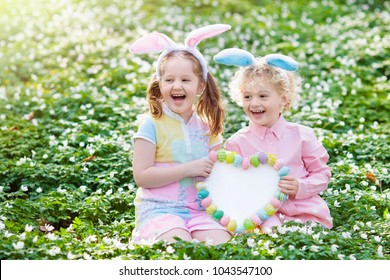 Easter egg hunt in spring garden. Kids searching for colorful eggs and sweets hidden in blooming flower field. Children with bunny ears. White board for your text. Family Easter celebration