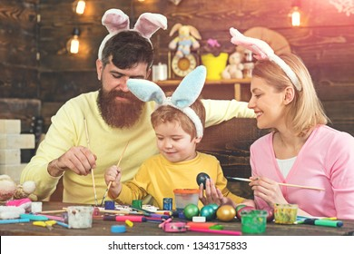 Easter egg ideas for happy family. Mother, father and son painting Easter eggs witht easter bunny costume and fake bunny ears.