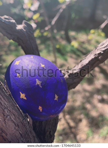 Easter egg painted blue, with golden ornaments, stuck in a tree branch. Perfect spot for Easter egg hunting. Close up.