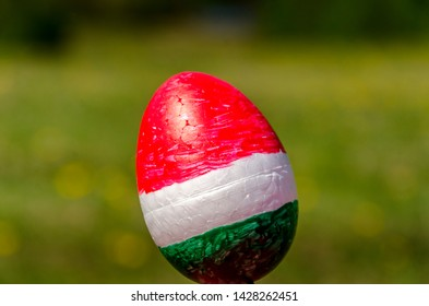 Easter egg painted in Hungarian flag colors on blurred grass background