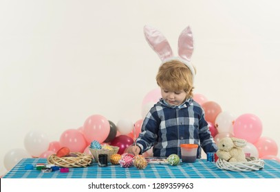 Easter egg painting. Cute child wiht bunny ears draws eggs for a holiday