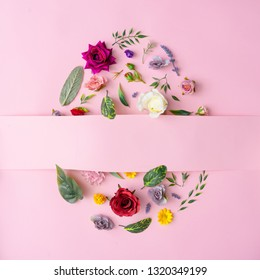Easter egg shape made with various spring flowers and leaves on pastel pink background. Minimal Happy Easter concept. Flat lay.