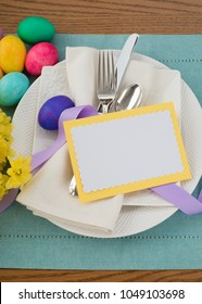 Easter Egg Table Setting with Menu or Invite Card with room or space for your words, text, copy, A flat flat layout with plate, silverware, flowers, and napkin from above looking down view.