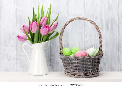 Easter eggs in baasket and pink tulips bouquet on shelf in front of wooden  wall