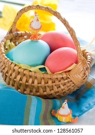 Easter eggs in basket with daffodil, selective focus